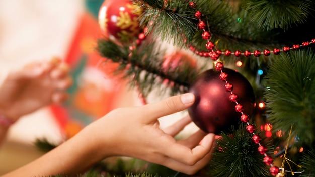 Imagens de closeup 4k de mão feminina pendurada e ajustando enfeites coloridos na árvore de natal. casa de decoração familiar nas festas e feriados de inverno.
