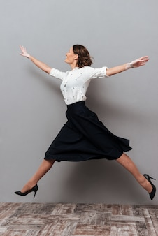 Imagens de corpo inteiro de mulher com roupas de negócios pulando e correndo no estúdio em cinza