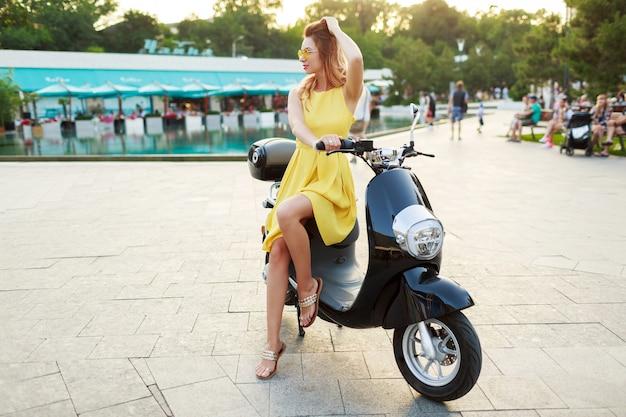 Imagens de corpo inteiro de mulher elegante e despreocupada com vestido amarelo brilhante, posando de moto retrô. dia ensolarado de verão.