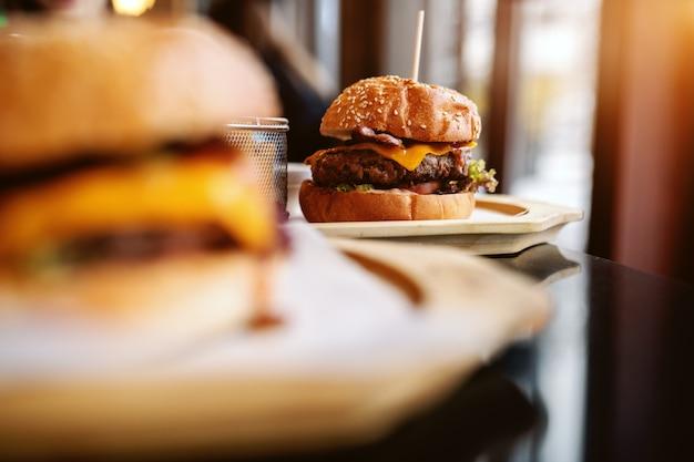 Imagens de deliciosos hambúrgueres na mesa. foco seletivo no hambúrguer no fundo.
