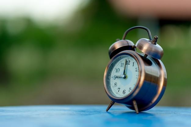 Imagens de despertador dourado colocado sobre uma mesa azul, fundo verde conceito pontual com espaço de cópia