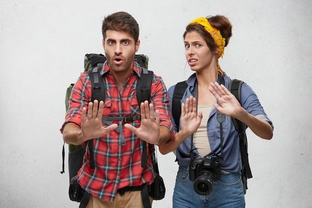 Imagens de elegantes jovens turistas masculinos e femininos europeus, viajantes ou aventuras parecendo frustrados e preocupados, mostrando o gesto de parada com as mãos, tentando resolver conflitos durante a viagem