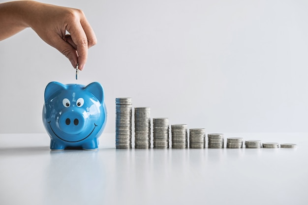 Imagens de empilhamento de moedas e mão colocando moedas no cofrinho azul para o planejamento aumentam o crescimento e as economias com caixa de dinheiro, economizando dinheiro para o plano futuro e o conceito de fundo de aposentadoria
