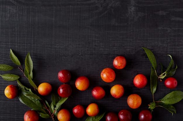 Imagens de estilo escuro criativo de ameixas e apriches cercado, vista superior de frutas frescas na mesa de madeira preta com espaço de cópia. composição fresca de verão. copie o espaço para propaganda.