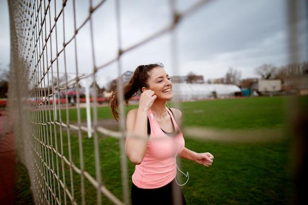 Imagens de execução sorridente jovem atraente garota fitness através da rede perto do campo de futebol.