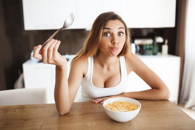 Imagens de garota jovem e atraente comendo flocos de milho com leite na cozinha e tirando sarro