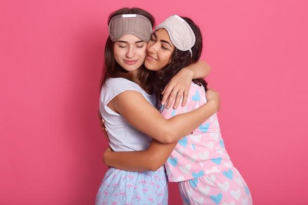 Imagens de lindas irmãs amigáveis e bonitas se abraçando, fechando os olhos, tendo expressão facial, indo para a cama