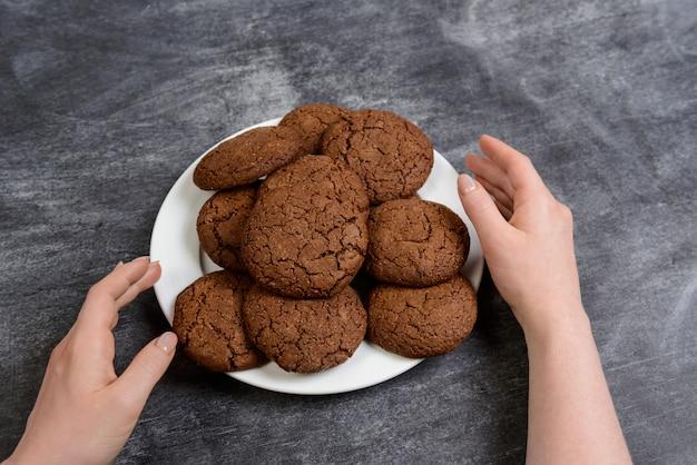 Imagens de mãos segurando biscoitos de chocolate sobre a superfície de madeira