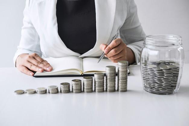 Imagens de moedas de empilhamento de crescimento e mão de mulher de negócios colocando moedas em uma garrafa de vidro (caixa de dinheiro) para planejar o aumento do lucro comercial e aumentar a economia, o plano futuro e o fundo de aposentadoria