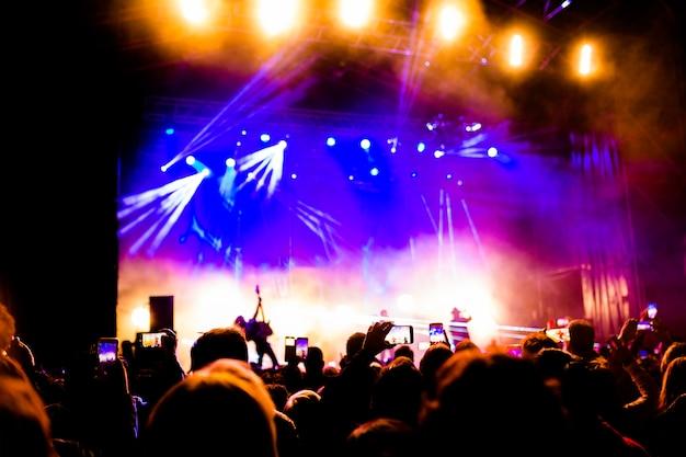 Imagens de muitas pessoas curtindo o desempenho noturno, grande multidão irreconhecível dançando com as mãos levantadas e os telefones celulares em concerto. vida noturna