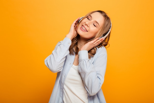 Imagens de mulher bonita caucasiana 20 anos usando aparelho em roupas casuais, ouvindo música usando fones de ouvido sem fio, isolados sobre o espaço amarelo