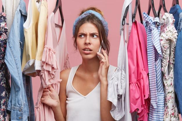 Imagens de preocupada bela caucasiana jovem de pé no guarda-roupa entre roupas de verão e falando no celular para um amigo pedindo ajuda para escolher o vestido perfeito para usar na data