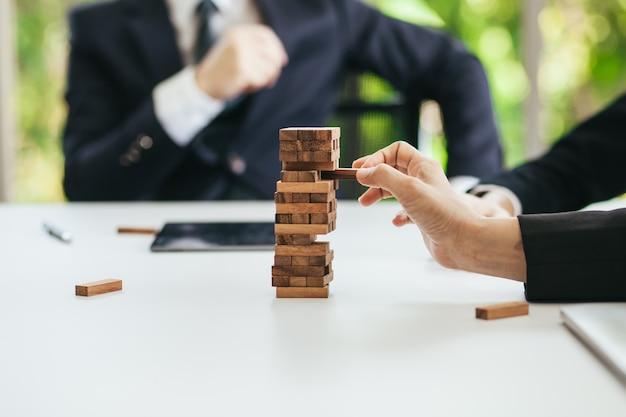 Imagens de risco de negócio pessoas de negócios estão analisando planos para puxar blocos de madeira.