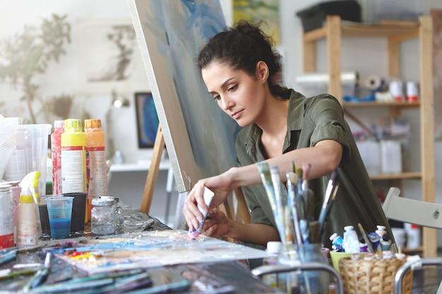Imagens de sério concentrada jovem artista feminina caucasiana, sentado na mesa com acessórios de pintura, segurando o tubo de tinta a óleo, misturando cores na paleta; pintura inacabada sobre tela perto dela