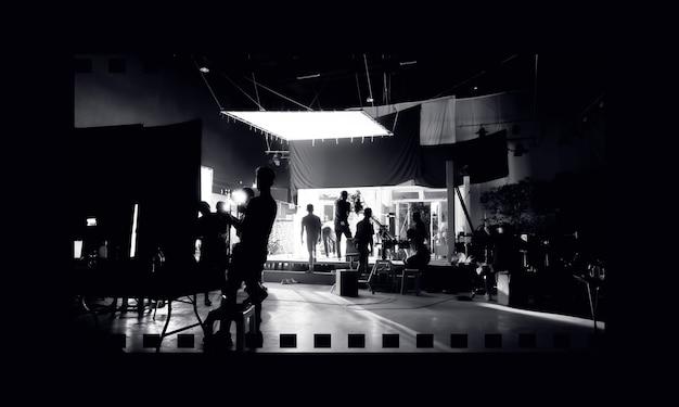 Imagens de silhueta de produção de vídeo nos bastidores ou b-roll ou making of de comerciais de tv que a equipe de filmagem equipa o lightman e o cameraman de vídeo trabalhando em conjunto com o diretor de cinema no estúdio.