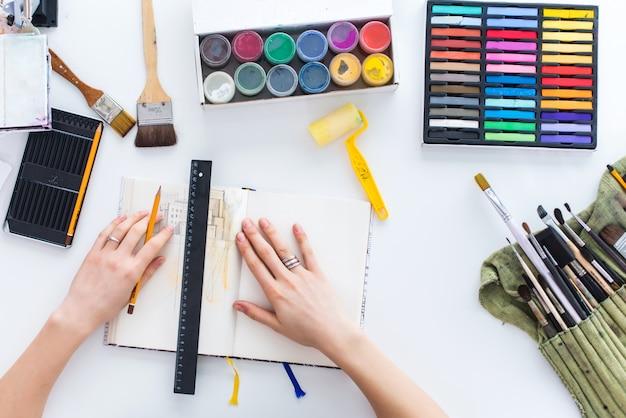 Imagens de vista superior do pintor desenhando esboço no caderno de desenho usando lápis, giz de cera e tintas guache. artista pintando na oficina.