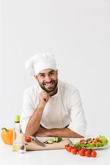Imagens do chef jovem feliz otimista em uniforme cozinhando com legumes frescos.