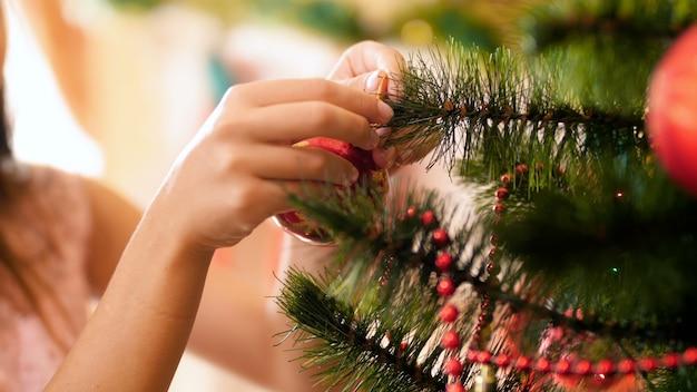 Imagens do close up das mãos femininas penduradas bugigangas coloridas na árvore de natal. casa de decoração familiar nas festas e feriados de inverno.