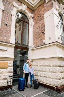 Imagens do jovem casal entrando no hotel. jovem e mulher em pé perto do antigo edifício hotel da cidade, ao ar livre, segurando malas
