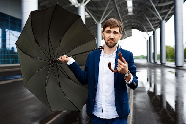 Imagens do jovem empresário confuso na rua segurando guarda-chuva quebrada
