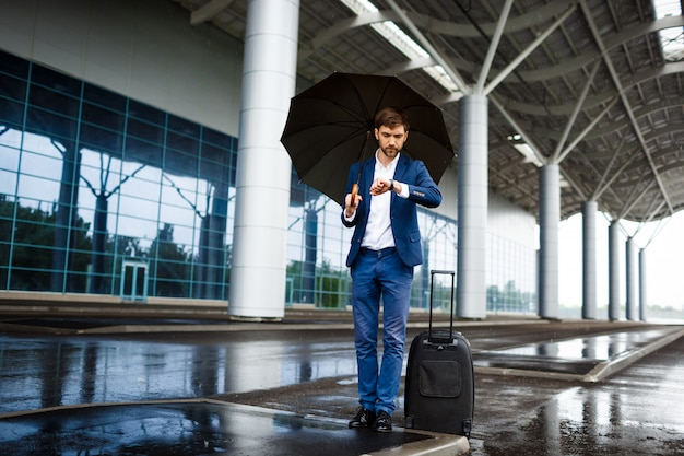 Imagens do jovem empresário segurando a mala e o guarda-chuva, olhando no relógio, esperando na estação chuvosa