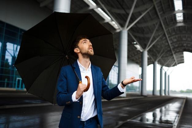 Imagens do jovem empresário segurando guarda-chuva na chuva, olhando para as gotas