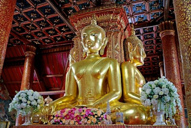 Imagens douradas do buda sentado de quatro lados do templo wat phumin na província de nan, tailândia