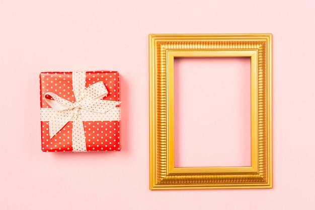 Imagens em branco vazio moldura dourada e caixa de presente vermelha sobre fundo rosa claro.