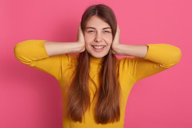 Imagens horizontais de alegre positiva jovem bonita tendo expressão facial agradável, estar de bom humor, vestindo roupas casuais, cobrindo os ouvidos com as mãos.
