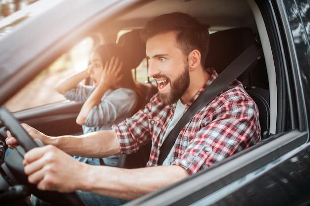 Imagens horizontais de cara emocional e confiante, dirigindo o carro. ele está olhando para a frente e gritando. a menina está espantada e olhando diretamente para a estrada.