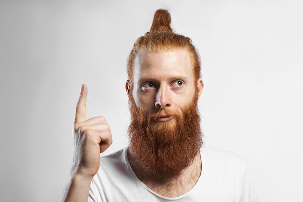 Imagens horizontais de emocional engraçado jovem com barba por fazer com penteado na moda e barba por fazer, tendo uma boa ideia, levantando o dedo e olhando para longe com um sorriso misterioso pensativo. linguagem corporal