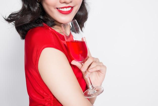 Imagens recortadas de jovens celebrando mulher asiática em vestido vermelho, segurando uma taça de vinho.