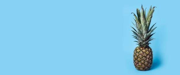Imagens verticais de abacaxi fresco maduro sobre uma superfície azul. bandeira