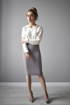 Imagens verticais de uma linda jovem europeia elegante em uma blusa branca elegante e saia tubo, segurando a mão no braço, olhando para a câmera com olhar sério e confiante. estilo, beleza, glamour e moda