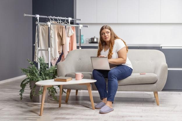 Imaginando, olhando para a janela, jovem gorda trabalhando em um laptop, sentada no sofá em casa com a cozinha