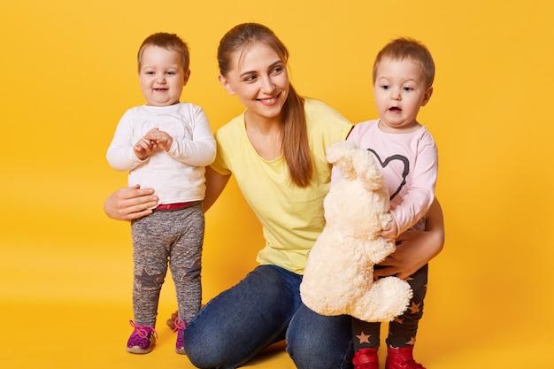 Imagine a jovem mãe linda com garotinhas gêmeas posando isoladas sobre amarelo