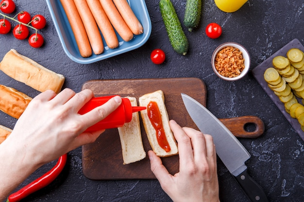Imagine em cima da mesa com ingredientes para cachorros-quentes, tábua de cortar, mãos de homem