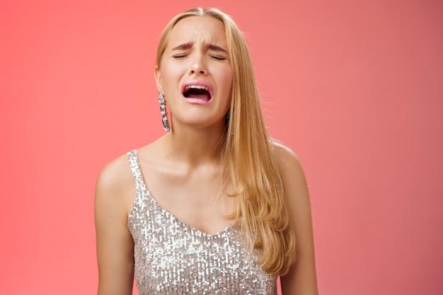 Imatura choramingando adulta mimada filha rica loira em um vestido prateado elegante reclamando triste, cruel vida injusta, chorando soluçando franzindo a testa amuada chateada, em pé decepcionado com um fundo vermelho