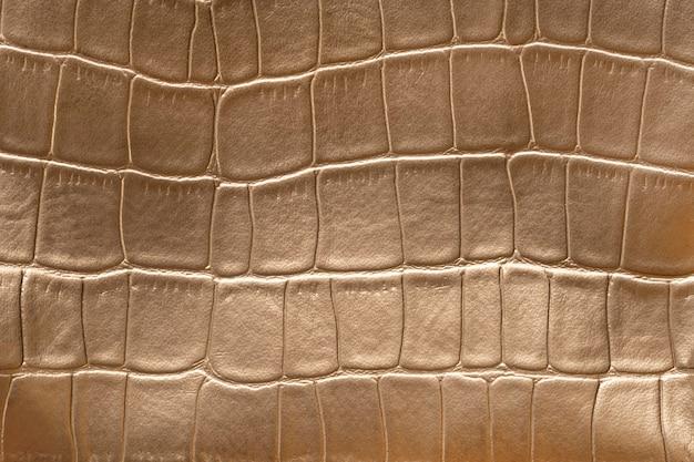 Imitação de padrão de pele de cobra dourada feita de couro sintético.