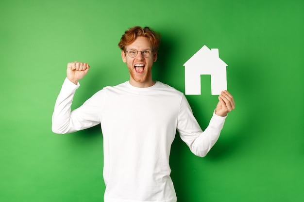 Imobiliária. feliz homem caucasiano de óculos com cabelo vermelho comemorando, mostrando o recorte da casa de papel e fazendo sinal de bomba de punho, gritando de alegria, comprando a propriedade, fundo verde.
