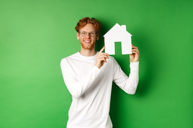 Imobiliária. jovem bonito, com cabelo ruivo, de óculos, mostrando o recorte da casa de papel e sorrindo, de pé contra um fundo verde.