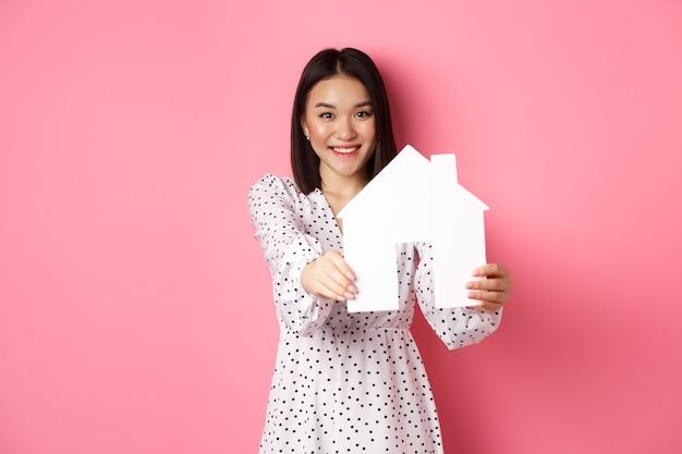 Imobiliária. mulher asiática adulta procurando por casa, segurando o modelo da casa e sorrindo, promo da corretora, em pé sobre fundo rosa