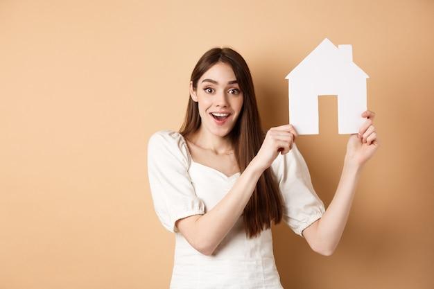 Imobiliária. mulher empolgada ganhou apartamento novo, mostrando recorte de casa de papel e sorrindo feliz, em pé sobre bege.