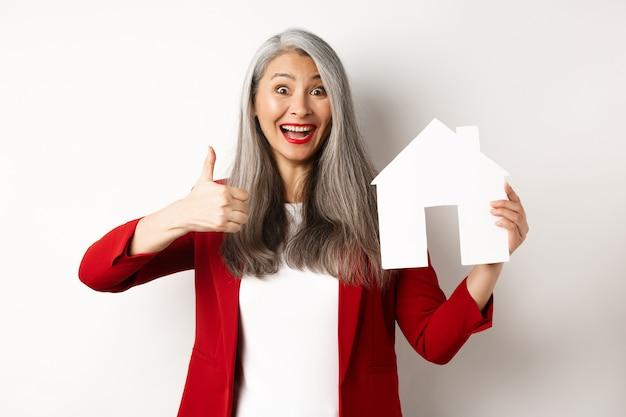 Imobiliária. retrato do corretor feminino asiático mostrando o polegar para cima e o recorte da casa de papel, recomendando a agência para comprar a propriedade, em pé feliz sobre o fundo branco.