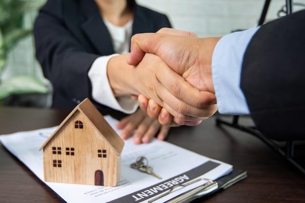 Imobiliário, aperto de mão e assinar o conceito de contrato, vendedor e comprador de casa bem sucedida negociar e conquista para acordo e apertar a mão juntos