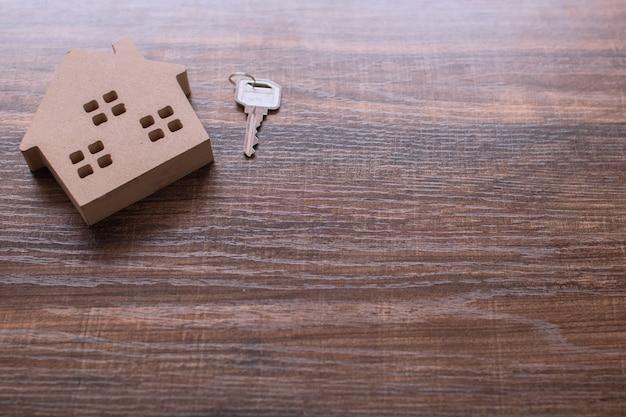Imobiliário com modelo de casa e chave na mesa de madeira