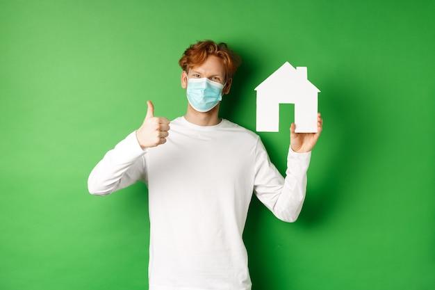 Imobiliário e conceito de pandemia covid-19. homem jovem ruivo com máscara médica, mostrando o recorte da casa de papel e mostrando o polegar para cima em aprovação, recomendando a agência.