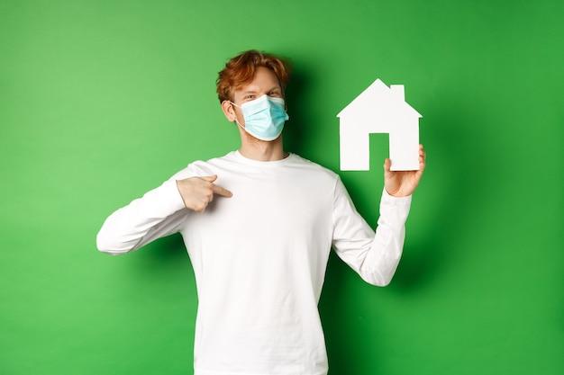 Imobiliário e conceito de pandemia covid-19. homem ruivo sorridente na máscara facial apontando para o recorte da casa de papel, mostrando a agência corretora, em pé sobre um fundo verde.