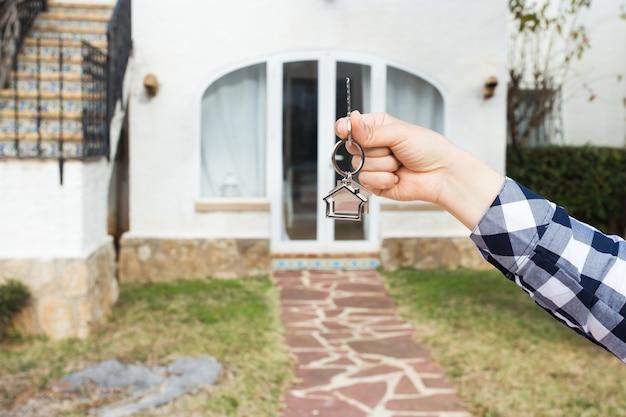 Imobiliário e conceito de propriedade - a mão está segurando as chaves da casa em um chaveiro em forma de casa na frente de um