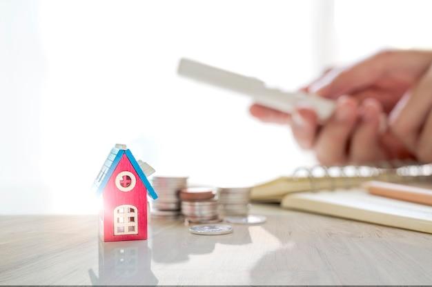 Imobiliário e conceito de propriedade, modelo de casa, pilha de moedas na mesa de madeira